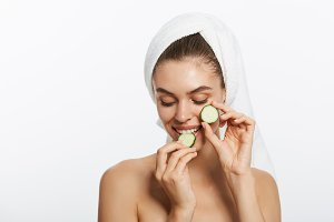 Woman with facial mask and cucumber