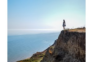 The girl is standing on a cliff near