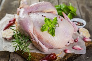 Raw whole chicken with herbs and