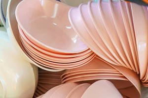 Many dishware stacked on table