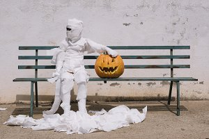 Little mummy boy with a pumpkin sitt