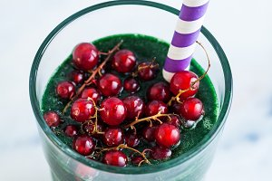 a tall glass of green fruit smoothie