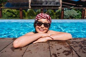 Girl teenager in a pool side looking