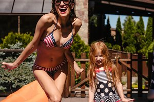 Mom and daughter near the pool, outd