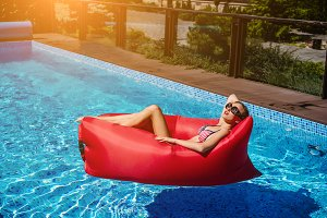 woman on red lounger in pool