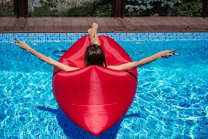 woman on red lounger in the pool