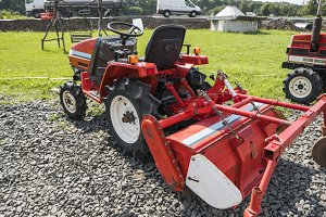 A small mini red tractor stands on a