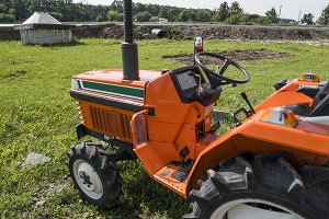 A small mini orange tractor stands