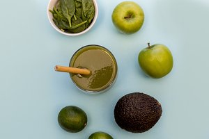 Green smoothie drink blue background