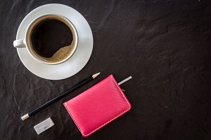 Cup of coffee with notebook and pen