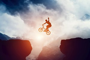 Man on bike jumping over precipice