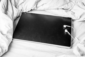 Black laptop on the bed