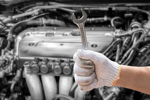 Hand holding wrench on car engine
