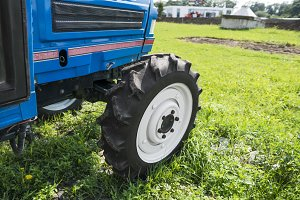 A small mini blue tractor stands on