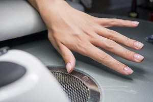 Woman having a nail manicure in a