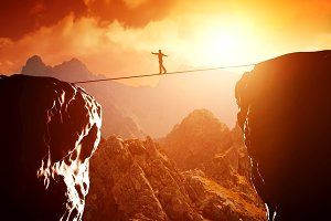 Man balancing on rope over precipice