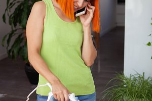 Redhead woman l ironing clothes whil