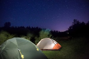 Tents in mountains under night sky
