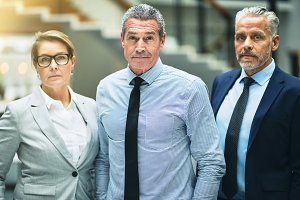 Confident mature businessman and two