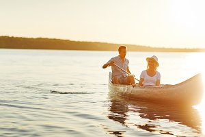 Smiling young couple canoeing togeth