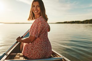 Smiling woman canoeing on a lake in