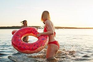 Two woman wearing swimsuits splashin