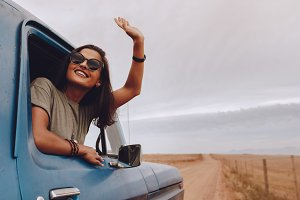 Happy woman enjoying road trip