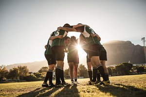 Rugby players huddling on sports