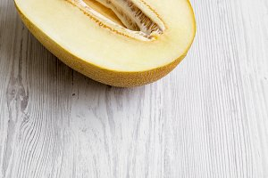 Half of melon on white wooden