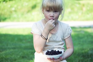 Funny soiled child eats blueberries