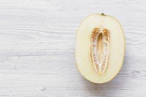 Half of melon on white wooden
