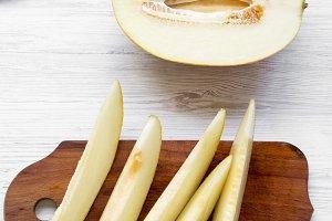 Melon slices over white wooden