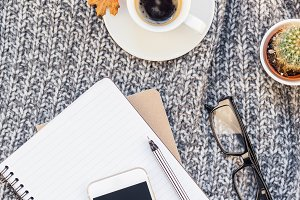 Home workplace with coffee cup on kn