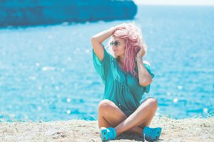 Woman with pink hair sitting on the