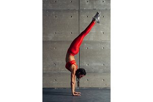 Young fit woman doing handstand