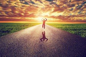 Happy man jumping on straight road