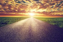 Long straight road under sunset sky