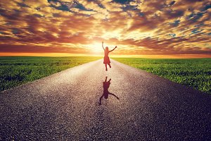 Happy woman jumping on straight road