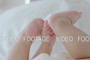 Baby lying on bed and touching feet