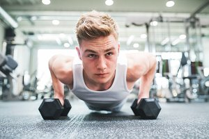 A close-up of young fit man in gym