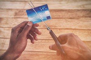 Man cutting credit card with scissor
