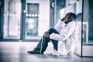 Worried doctor sitting floor