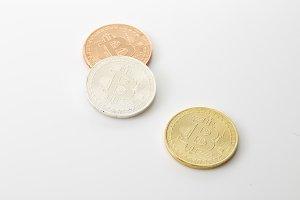 Three Bitcoins Coins on white