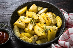 Baked potato with herbs in the pan.