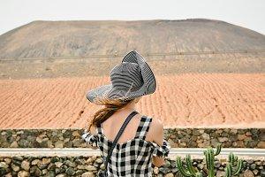 Girl traveler looking at volcano