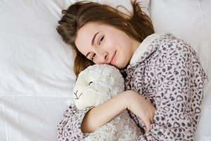 Teen girl sleeping with toy