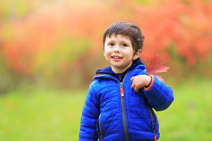 Boy with a red maple leaf
