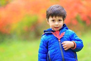 Portrait of a cute boy & maple leaf