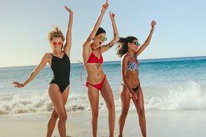 Women dancing on beach raising hands