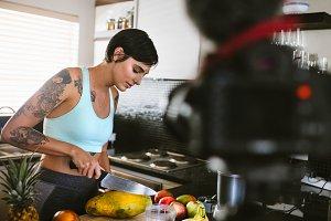 Vlogger in kitchen recording video